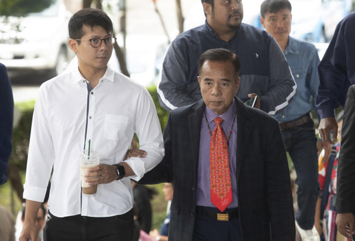 Veera Musigapong, front right, one of the leaders of Red Shirt, arrives at the Bangkok Criminal Court in Bangkok, Thailand, Wednesday, Aug. 14, 2019. The court has dismissed charges of terrorism and other offenses against 24 leaders of an extended street protest in 2010 that saw key parts of central Bangkok closed off and random violence that was ended by armed military force. (AP Photo/Sakchai Lalit)