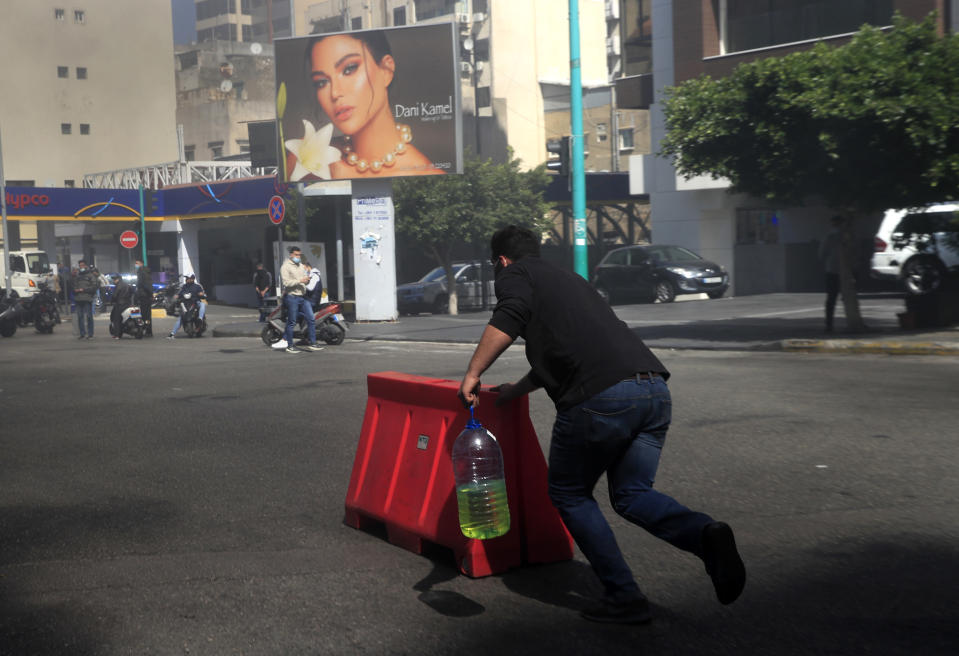 A protester pushes a plastic barrier and holds a container of gasoline to burn it to block a main road during a protest against the increase in prices of consumer goods and the crash of the local currency, in Beirut, Lebanon, Tuesday, March 16, 2021. Scattered protests broke out on Tuesday in different parts of the country after the Lebanese pound hit a new record low against the dollar on the black market. (AP Photo/Hussein Malla)