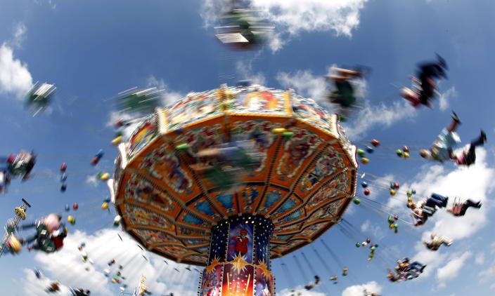 Visitors enjoy a ride in a carousel on a sunny day at the famous beer festival 'Oktoberfest' in Munich, southern Germany, on Wednesday, Sept.21, 2011. The world's biggest beer festival runs until October 3. (AP Photo/Matthias Schrader)