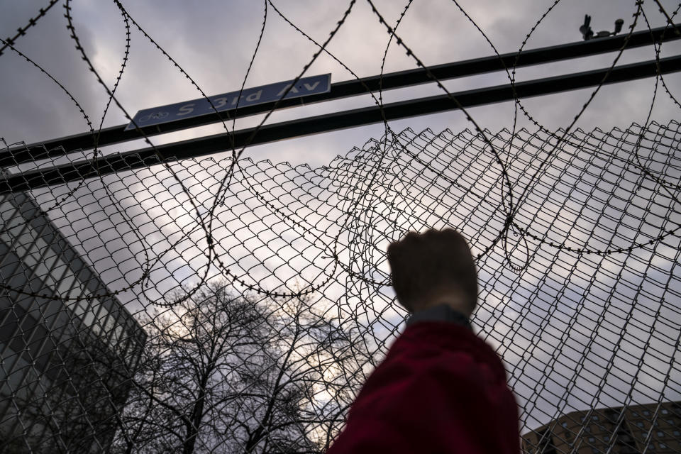 Demonstrators rally outside the Minneapolis 3rd Precinct guarded by perimeter security fences and razor wire as the murder trial against the former Minneapolis police officer Derek Chauvin in the killing of George Floyd advances to jury deliberations, Monday, April 19, 2021, in Minneapolis. (AP Photo/John Minchillo)
