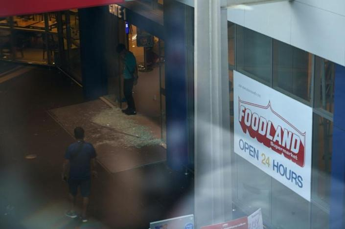 In the swirl of competing information, dread gripped those hidden inside cupboards, storerooms and toilets across the mall -- when it was over, people looked at glass smashed at the mall entrance (AFP Photo/CHALINEE THIRASUPA)