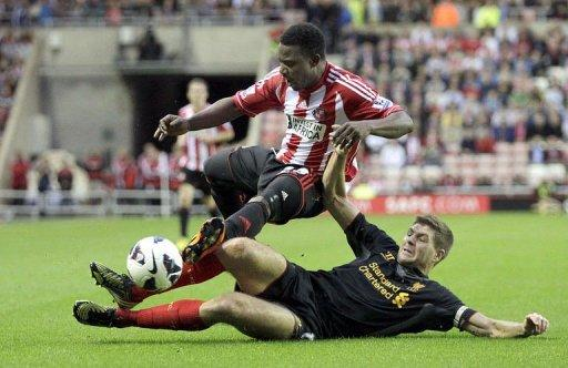 Sunderland's midfielder Stephane Sessegnon (L) is tackled by Liverpool's midfielder Steven Gerrard