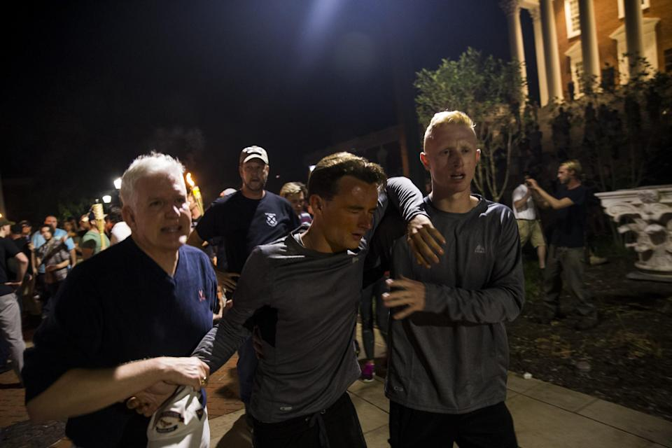 <p>A man is helped after being hit in the face with pepper spray during a clash between counter protestors and Neo Nazis, Alt-Right, and White Supremacist groups after they marched through the University of Virginia Campus with torches in Charlottesville, Va., on Aug. 11, 2017. (Photo: Samuel Corum/Anadolu Agency/Getty Images) </p>