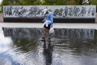 A man walks across a shallow water feature at the newly opened World War I Memorial, Friday, April 16, 2021, in Washington. (AP Photo/Jacquelyn Martin)