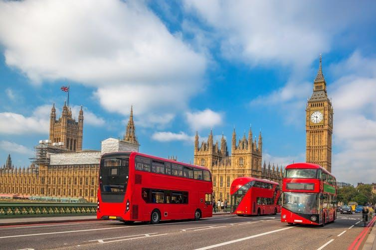 Three red buses drive on Westminster Bridge in London.