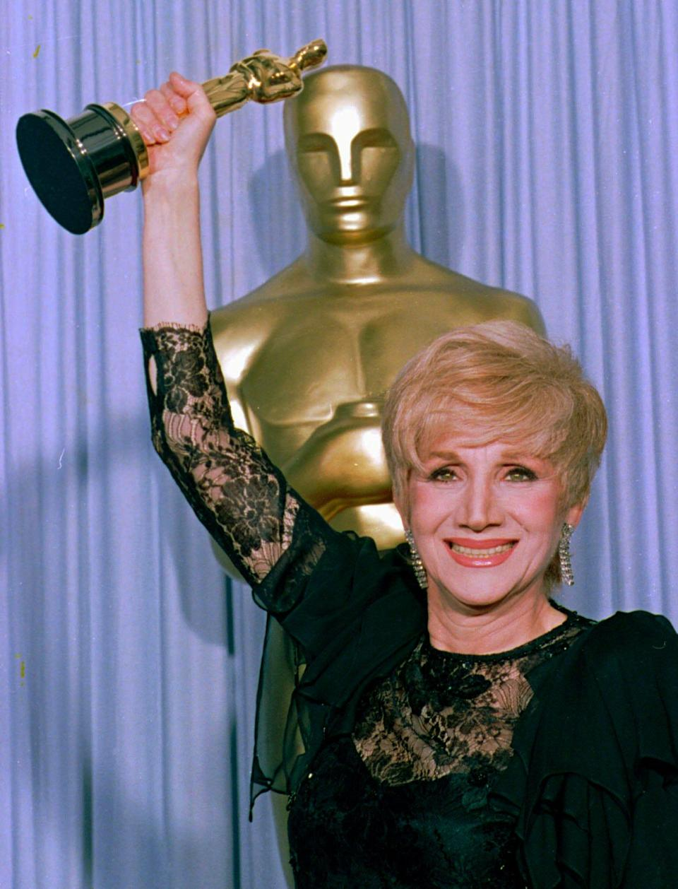 "Olympia Dukakis holds her best supporting actress Oscar for ""Moonstruck"" at the Academy Awards on April 11, 1988. The veteran stage and screen actress, who played Cher's mother in the film, was 89."
