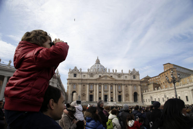 A child uses binoculars to watch Pope Francis delivering the Angelus from a window of the Apostolic palace in St. Peter's Square, at the Vatican, Sunday, Jan. 12, 2014. The pontiff has named his first batch of cardinals, choosing 19 men from Asia, Africa, North and South America and elsewhere, including Haiti and Burkina Faso, to reflect his attention to the poor. Francis made the announcement Sunday as he spoke from his studio window to a crowd in St. Peter's Square. (AP Photo/Gregorio Borgia)