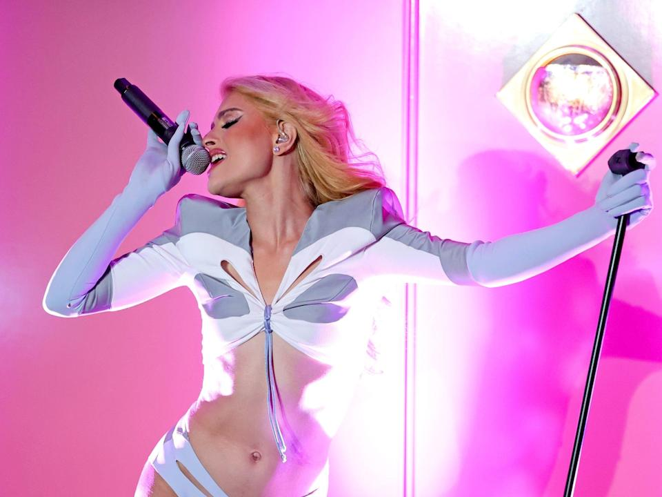 """Gia Woods performs onstage in a white and grey outfit in front of a pink background at the """"Thrive With Pride"""" concert."""