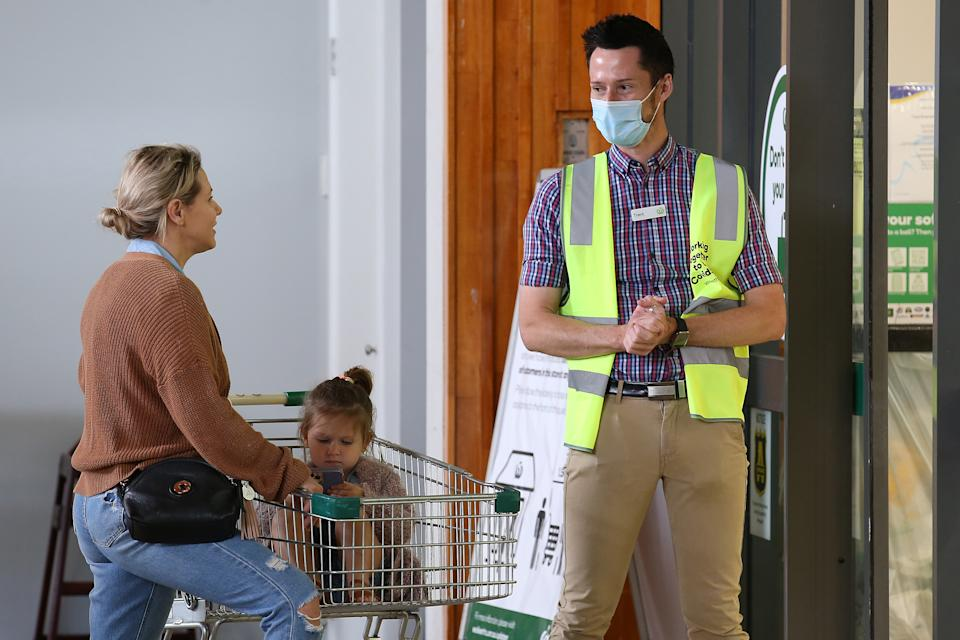 A worker controls speaks to a customer at the entrance to a Woolworths store. Source: Getty Images