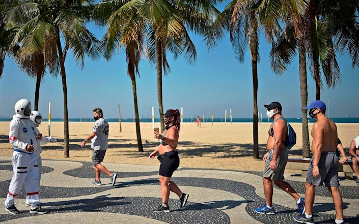 Brazilian accountant Tercio Galdino, 66, and his wife, Alicea, greet passers by as they walk along Copacabana beach in Brazil in protective suits - AFP