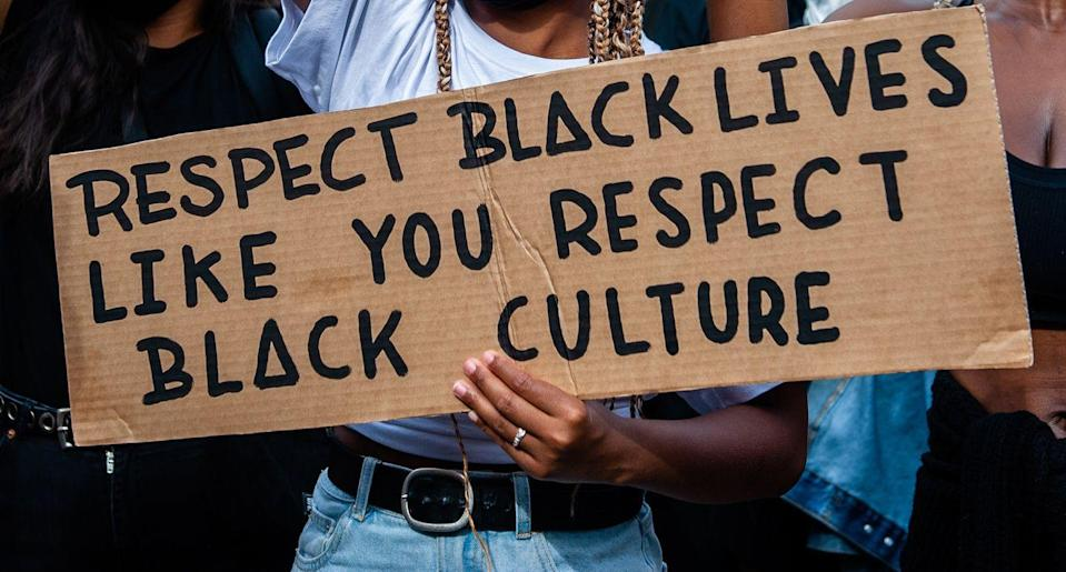 <p>A Black woman holds a sign asking for respect of Black people—in the same way that Black culture is accepted (and even glorifeid) by society.</p>