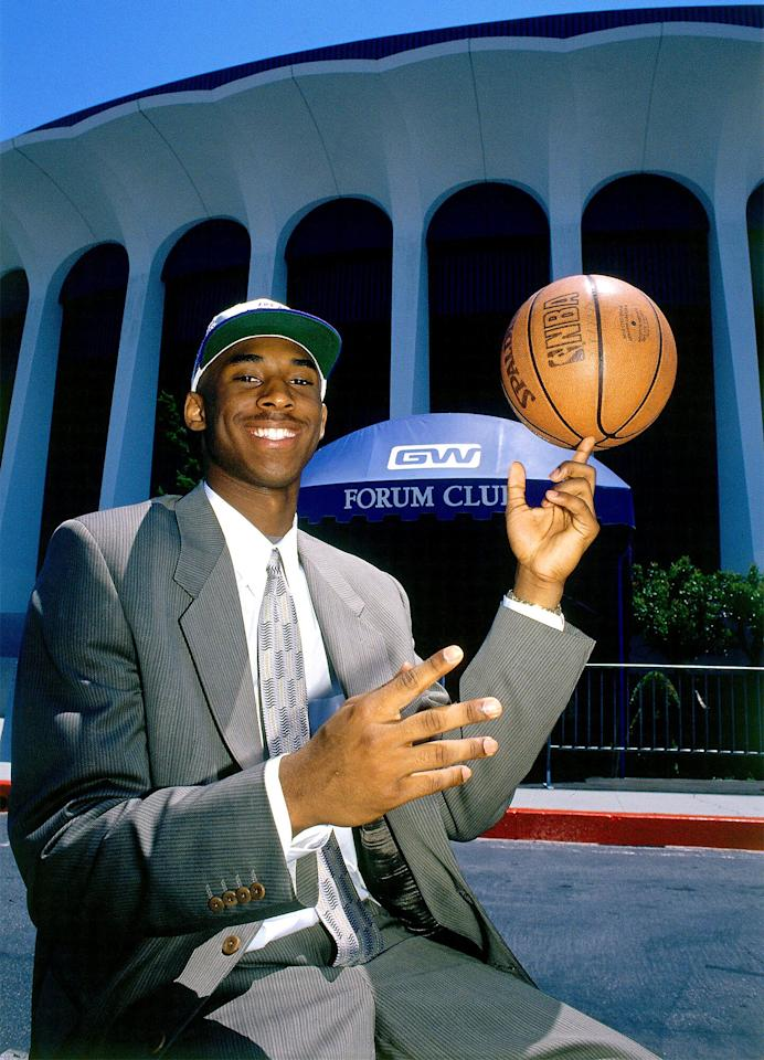 After earning his No. 8 Lakers number, Bryant is seen grinning while posing with a basketball outside the Forum in Inglewood, California, in 1997.