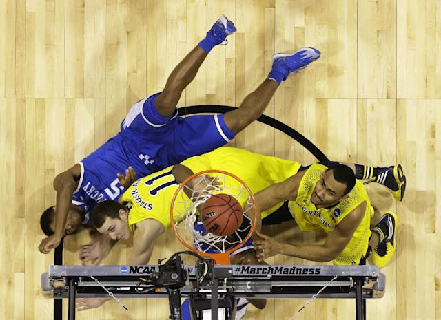 Michigan's Jon Horford, right, follows up a shot as players lay on the court during the first half of an NCAA Midwest Regional final college basketball tournament game against Kentucky Sunday, March 30, 2014, in Indianapolis. (AP Photo/Michael Conroy)