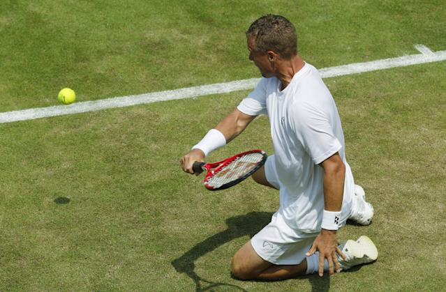 Lleyton Hewitt of Australia plays a shot from his knees to Michal Przysiezny of Poland during their first round match at the All England Lawn Tennis Championships in Wimbledon, London, Tuesday, June 24, 2014. (AP Photo/Ben Curtis)