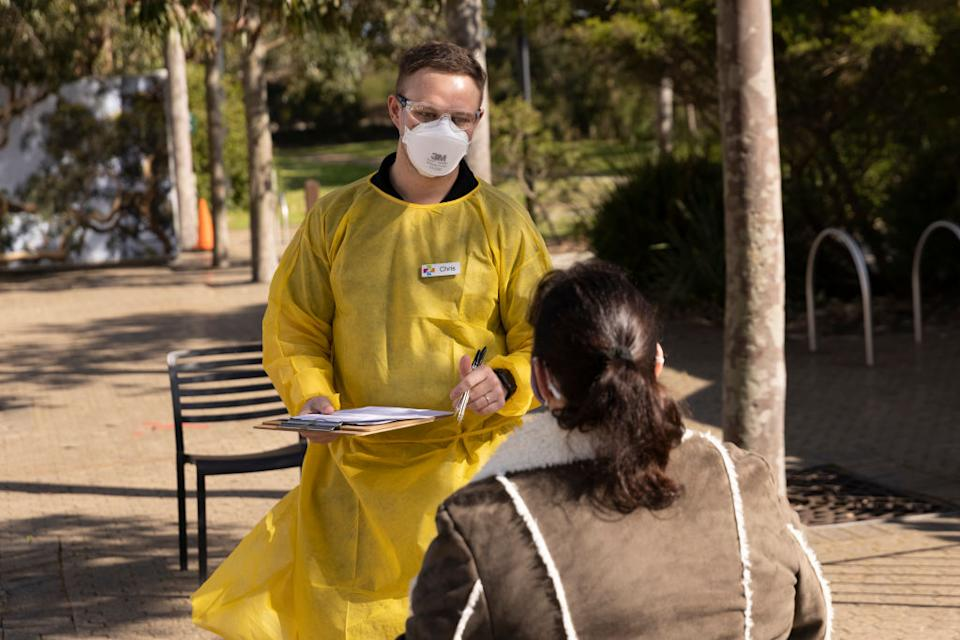 Medical worker Chris speaks to a patient waiting for their AstraZeneca vaccine at Taronga Zoo.