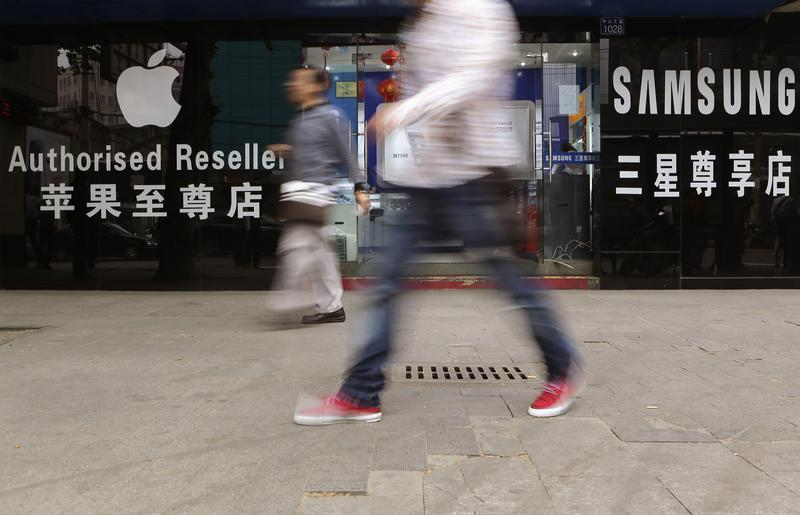 People walk past a mobile phone store selling Apple and Samsung products in Wuhan