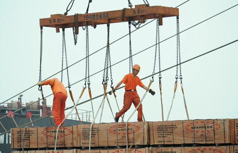 Workers load goods in a port in Lianyungang, east China's Jiangsu province on July 1, 2014. Chinese manufacturing picked up slightly in September