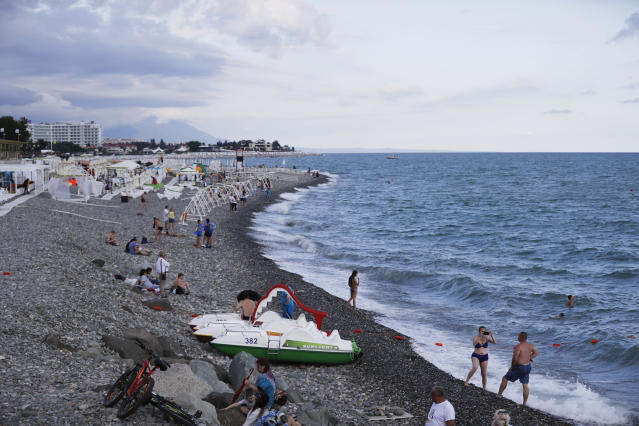 FILE - In this Saturday, June 23, 2018 filer, tourists enjoy the beach at the Black Sea in Sochi, Russia. Sochi in the summer is a whole lot different than what fans saw during the Winter Olympics. The snow is replaced by lots of sun as Russia's summertime playground explodes in a scene more akin to Southern California or Miami Beach than Siberia. World Cup fans have been taking advantage of the beaches, waterparks and other warm-weather activities, and teams have been eager to train there. (AP Photo/Rebecca Blackwell, File)
