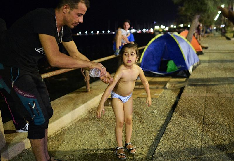 An Iraqi man washes his daugher with a bottle of water, before putting her to sleep at their unprovisioned camp in the center of the city of Kos island late on August 17, 2015 (AFP Photo/Louisa Gouliamaki)