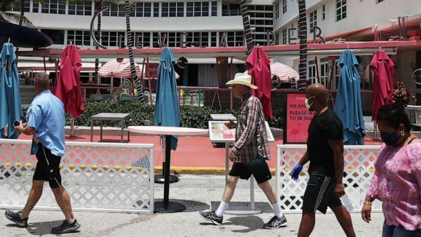 PHOTO: People walk past the Clevelander South Beach Hotel on July 13, 2020, in Miami Beach, Fla. The hotel announced it was closing again until further notice due to growing concerns about the Covid-19 pandemic in Miami-Dade County. (Joe Raedle/Getty Images)