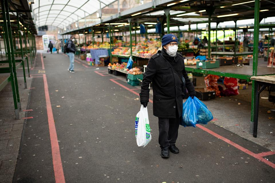 A shopper at a quiet market in Birmingham on Wednesday. MPs have retrospectively approved Boris Johnson's coronavirus lockdown for England. (Jacob King/PA)