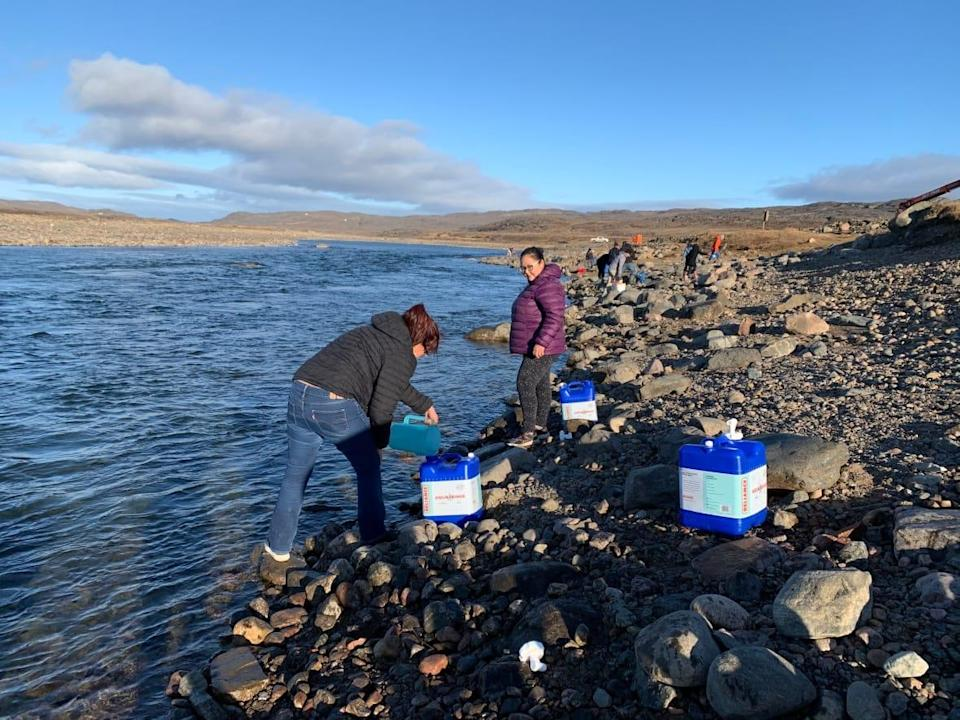 Residents collect water from the Sylvia Grinnell River near Iqaluit Wednesday, after city staff found evidence of fuel contamination in the city's treated water supply, making it undrinkable. (Emma Tranter/The Canadian Press - image credit)