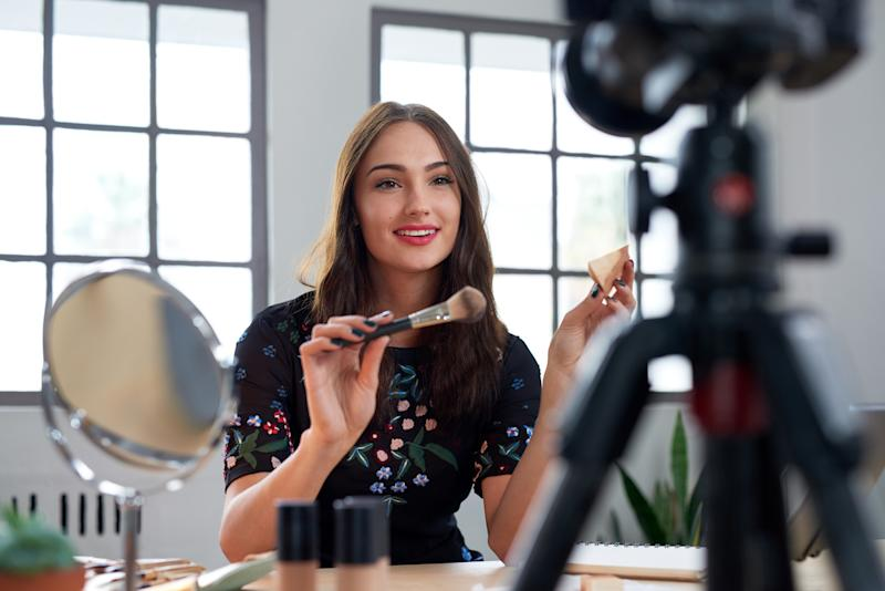 A beauty blogger films herself testing out cosmetics.