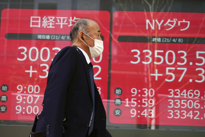 A man wearing a protective mask walks in front of an electronic stock board showing Japan's Nikkei 225 and New York Dow indexes at a securities firm in Tokyo Friday, April 9, 2021. Shares fell Friday in most Asian markets after China reported a stronger than expected rise in prices that could prompt authorities to act to cool inflation. (AP Photo/Eugene Hoshiko)