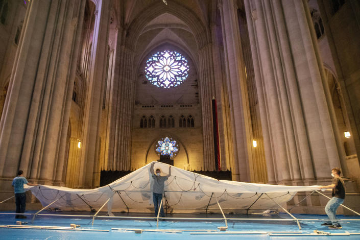 Volunteers raise a tent while building a field hospital at the Cathedral of St. John the Divine, Wednesday, April 8, 2020, in New York. Volunteers assembled and placed 56 beds in five chapels and raised one of several tents in the nave. Work will continue Thursday. (AP Photo/Mary Altaffer)