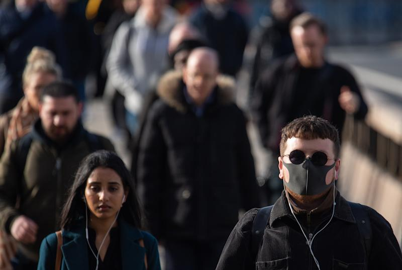 A man wearing a protective face mask as commuters cross London Bridge during morning rush hour in London , as the Government's top scientist warned that up to 10,000 people in the UK are already infected.
