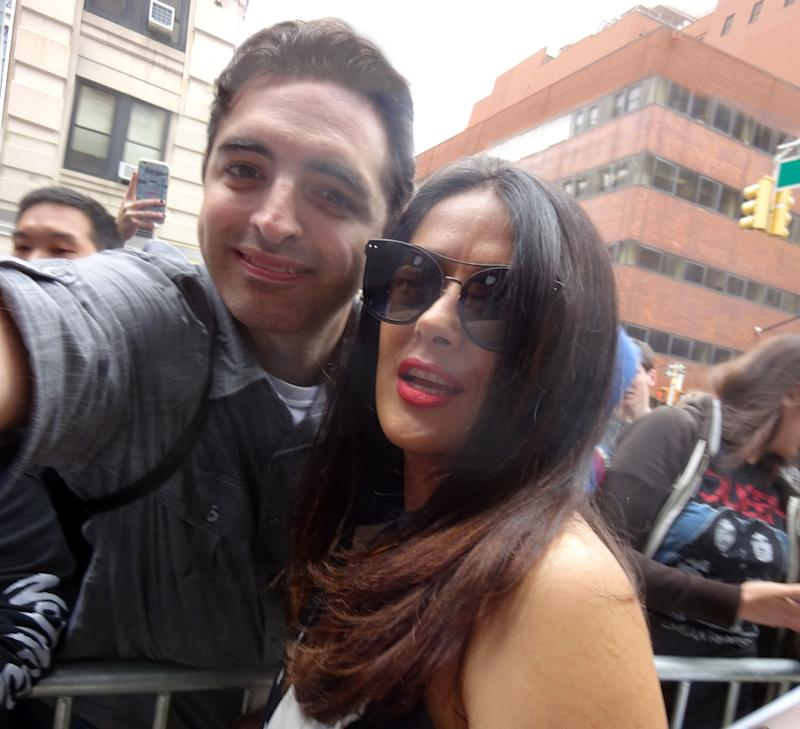 Salma Hayek smiles proudly for the camera with a male fan