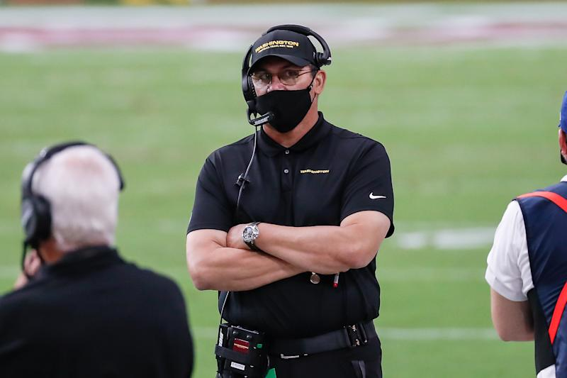Ron Rivera in a black mask stands on a field, arms crossed.