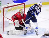 Winnipeg Jets' Pierre-Luc Dubois (13) takes a shot to the chest as he attempts to screen Ottawa Senators goaltender Matt Murray (30) during the third period of an NHL hockey game Wednesday, April 14, 2021, in Ottawa, Ontario. (Sean Kilpatrick/The Canadian Press via AP)