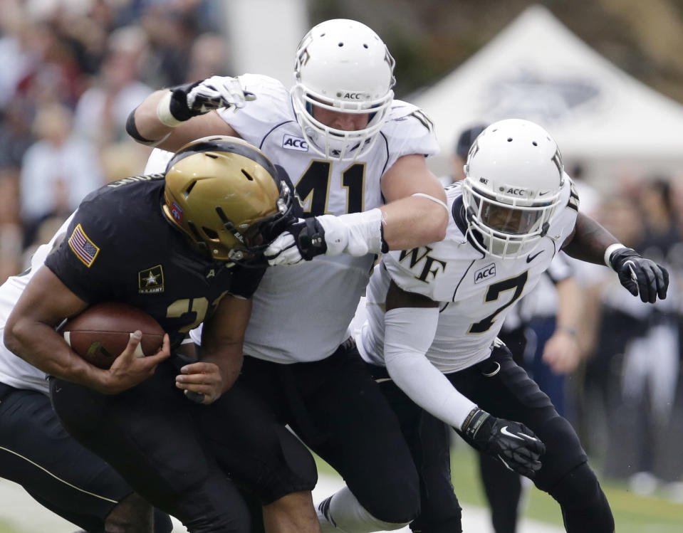Army running back Terry Baggett, left, is tackled by Wake Forest linebacker Mike Olsen (41) and cornerback Merrill Noel (7) during the first half of an NCAA college football game on Saturday, Sept. 21, 2013, in West Point, N.Y. (AP Photo/Mike Groll)
