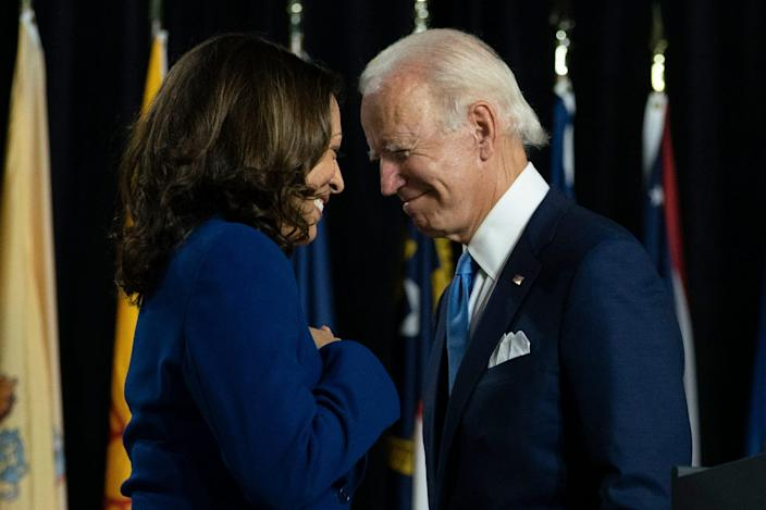 Democratic presidential candidate former Vice President Joe Biden and his running mate Sen. Kamala Harris, D-Calif., pass each other as Harris moves to the podium to speak during a campaign event at Alexis Dupont High School in Wilmington, Del. ()