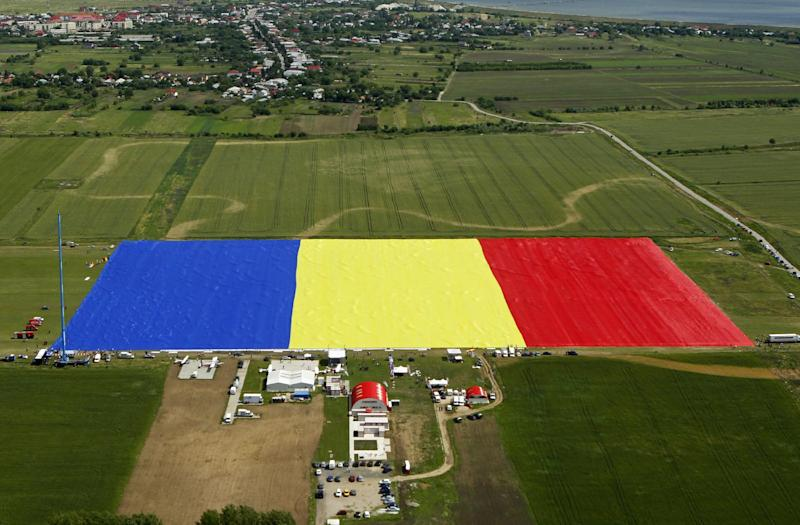 An aerial picture shows a huge Romanian flag on the Clinceni Airfield, south of Bucharest, Romania, Monday, May 27, 2013. Romania entered the Guinness Book of records after it unveiled the largest flag ever made. It took about 200 people several hours Monday to unfurl a five-ton flag of Romania which organizers said measured 349.4 meters by 226.9 meters, about three times the size of a football pitch.(AP Photo/Bogdan Cristel, Pool)