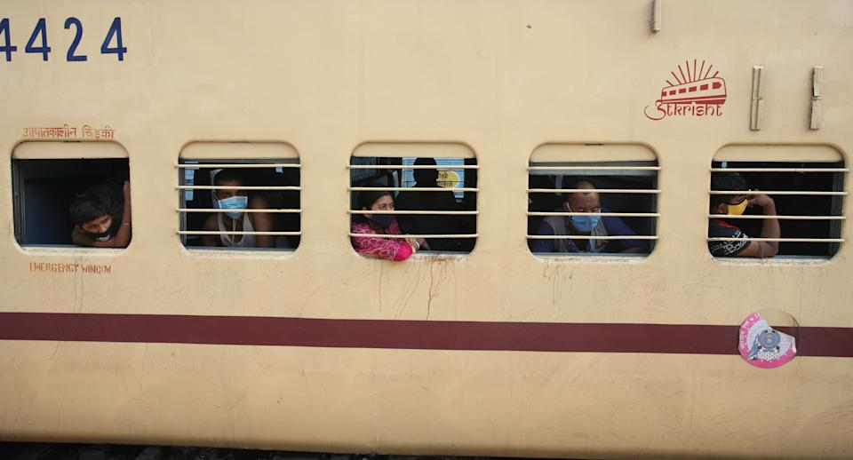 migrant workers peep out from  Shramik special train coming from Surat to howrah, as they wait for food and drinking water to be provided by Government , during nationwide lockdown as a preventive measure against COVID-19 coronavirus ,at a railway staion in Allahabad on May 30,2020 . (Photo by Ritesh Shukla/NurPhoto via Getty Images)