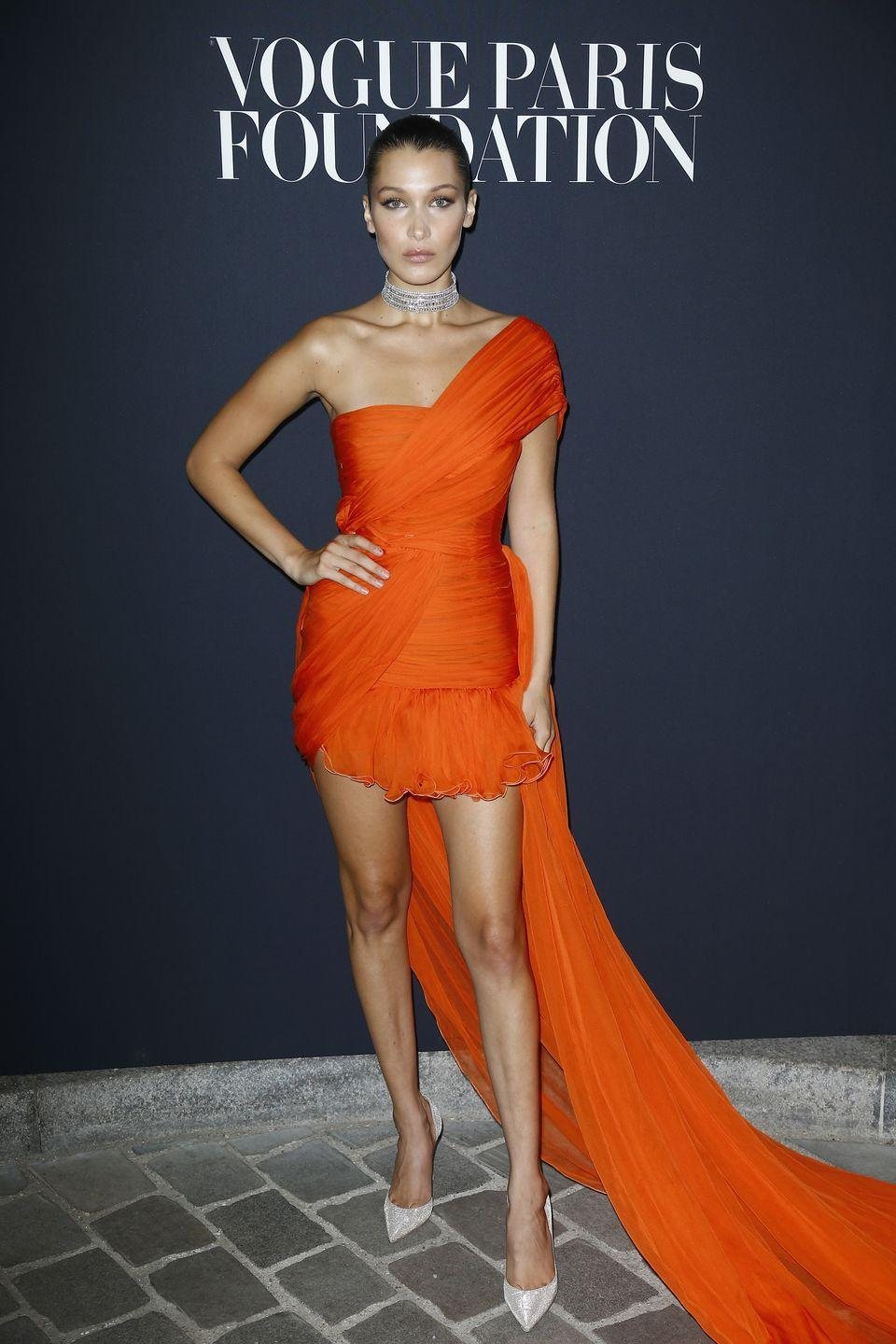 <p>Bella wears a bright orange, one-shoulder number with an exaggerated train for theVogue Foundation Dinner 2017, 4 July 2017</p>