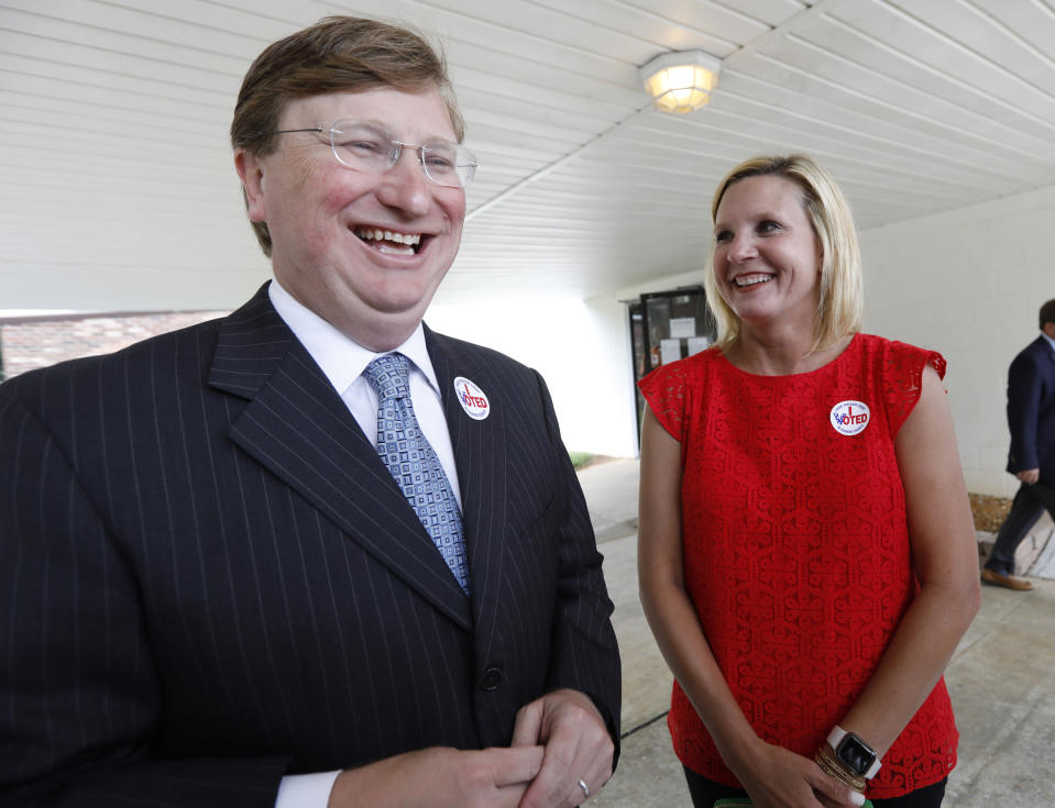 Lt. Gov. Tate Reeves, left, and his wife Elee Reeves, share a laugh as he speaks with reporters about the final days of the runoff campaign, for the GOP nomination for governor, Tuesday, Aug. 27, 2019 at his Flowood, Miss., voting precinct. Reeves faces former Mississippi Supreme Court Chief Justice Bill Waller Jr., for the party's nomination. (AP Photo/Rogelio V. Solis)