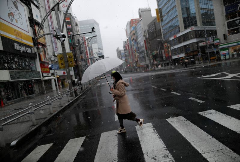 A woman wearing a protective face mask, following an outbreak of the coronavirus disease, walks past on a nearly empty street in a snow fall in Tokyo