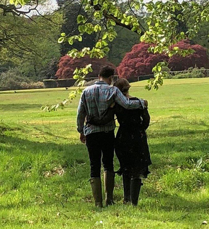 In a candid shot, the couple walk away from the camera with their arms around each other.