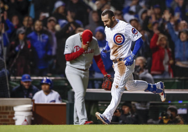 Chicago Cubs' Daniel Descalso, right, runs to score on a triple against the Philadelphia Phillies during the eight inning of a baseball game, Monday, May 20, 2019, in Chicago. (AP Photo/Kamil Krzaczynski)
