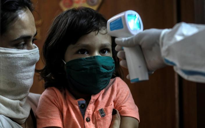 More from India, where a child gets their temperature checked during medical checkups at a residential building in Mumbai - Shutterstock