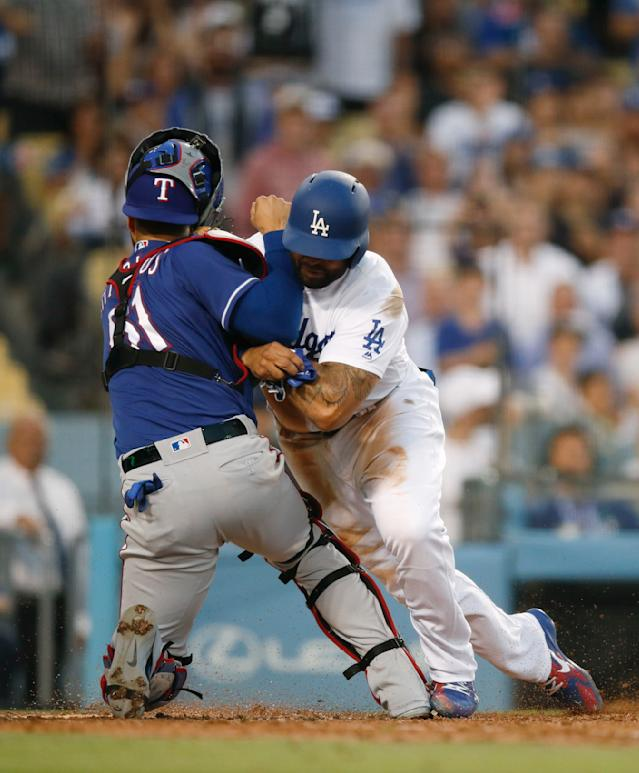 Los Angeles Dodgers' Matt Kemp, right, shoves Texas Rangers catcher Robinson Chirinos while trying to score on a single hit by Enrique Hernandez during the third inning of a baseball game Wednesday, June 13, 2018, in Los Angeles. (AP Photo/Jae C. Hong)