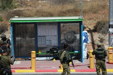 Israeli forces stand guard at the scene of what Israeli military said is a car-ramming attack near the settlement of Elazar in the Israeli-occupied West Bank