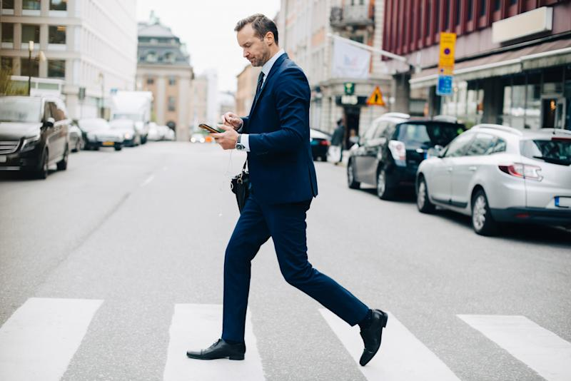 Full length side view of mature businessman crossing street while using smart phone in city