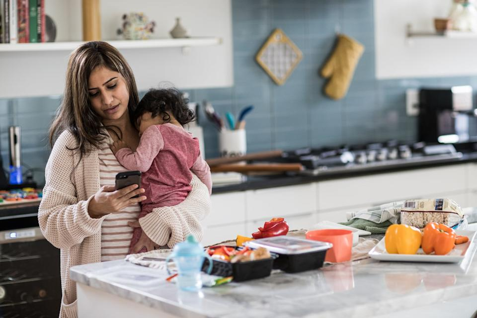Mother holding baby and multi-tasking in kitchen