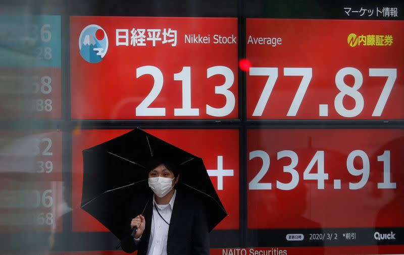 A visitor wearing protective face mask, following an outbreak of the coronavirus, walks past in front of an electric screen displaying Nikkei share average outside a brokerage in Tokyo