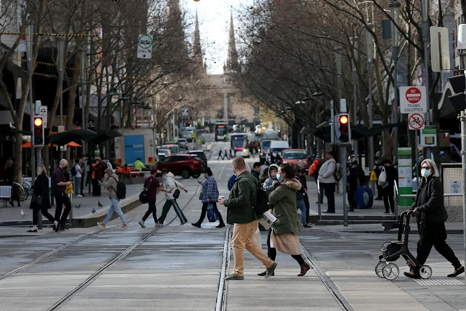 Melbourne residents cross a busy street.