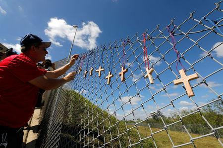 Chaplain places crosses for the victims of the Marjory Stoneman Douglas High School shooting in Parkland